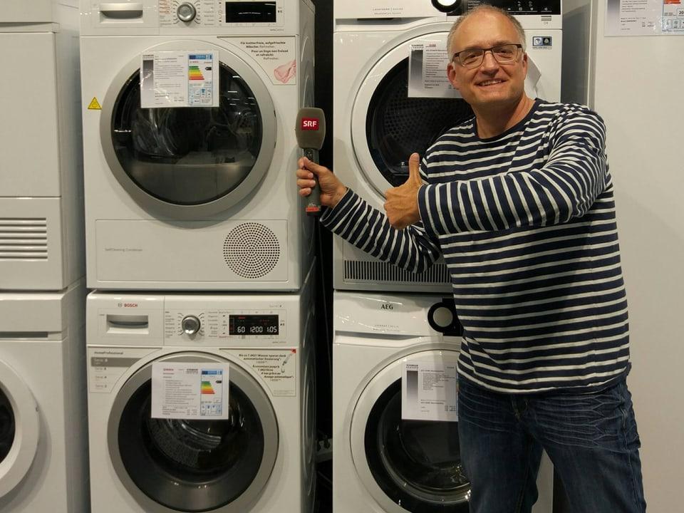 Marcel vor gestapelten Waschmaschinen