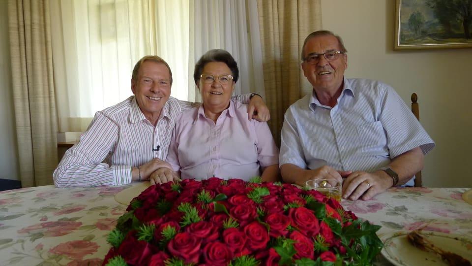 Herr und Frau Jakob sitzen mit Kurt Aeschbacher am Tisch, vor sich ein Blumengesteck in Herzform aus roten Rosen.