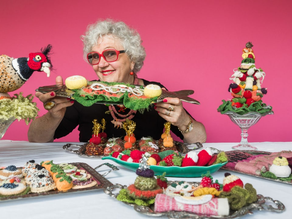 Madame Tricot sitzt an einer Theke mit vielen gestrickten Waren.