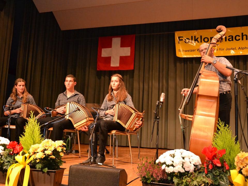 Zwei junge Frauen und ein junger Mann spielen Schwyzerörgeli.