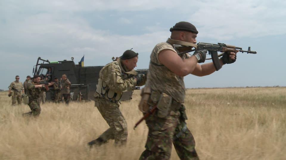Bewaffnete Männer ziehen durchs Feld.