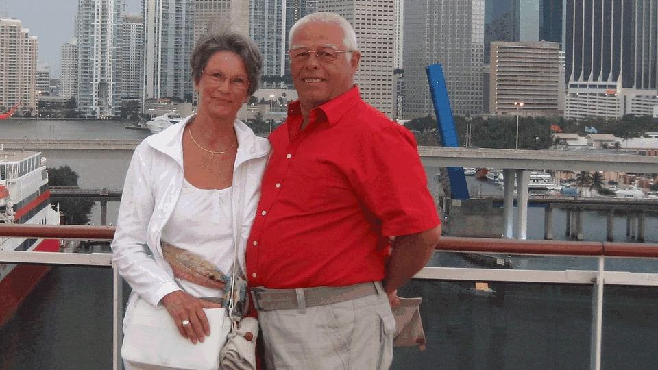 Doris Dössegger und Hermann Merz posieren vor einem Hafen und Wolkenkratzern.
