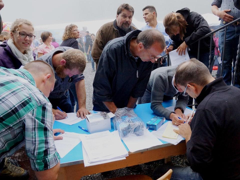 Eine Traube von Menschen versammelt sich um den Tisch, an dem Guido Rüegge sitzt.