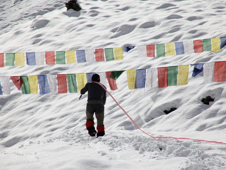 Mann stapft mit Wasserschlauch über der Schulter durch verschneite Landschaft.