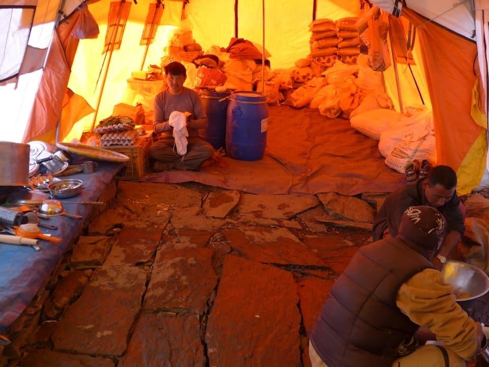 Im Zelt sitzen Männer und trocknen ab.