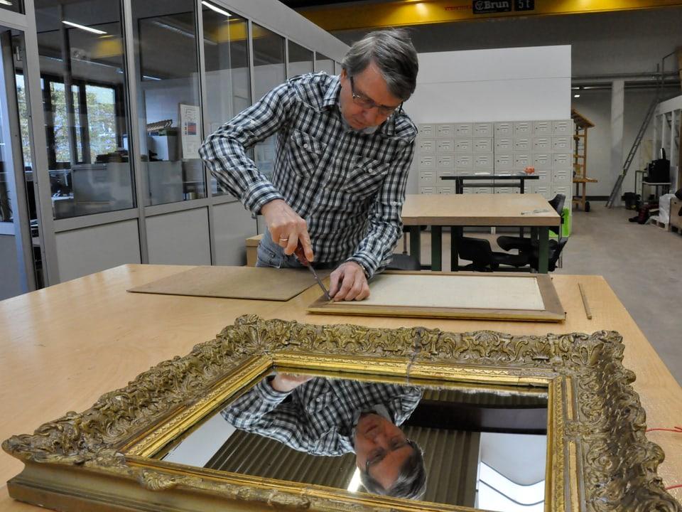 Ein Mann arbeitet mit einem Schneidemesser an einem Bilderrahmen