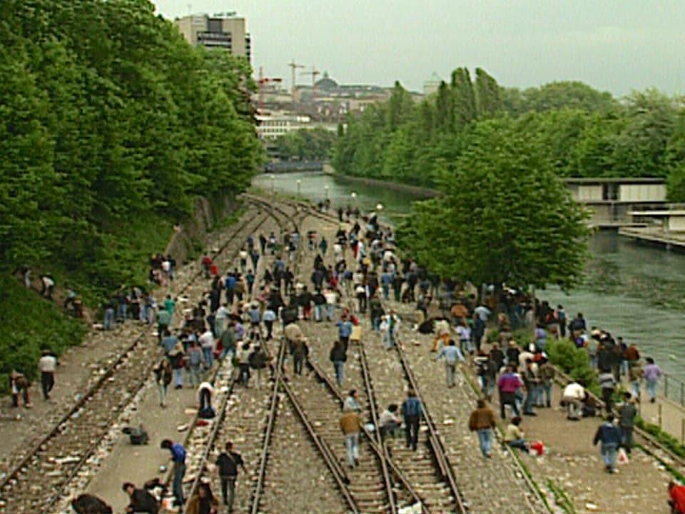 Menschen auf Zuggeleise neben der Limmat. Die offene Drogenszene am Letten.