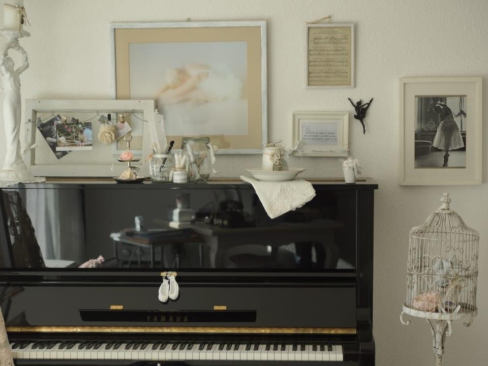 Bilder und Kerzenständer über Klavier.