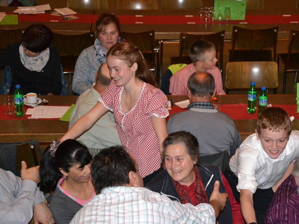 Händeschütteln an den Tischen, an denen Musikanten und Publikum sitzen.