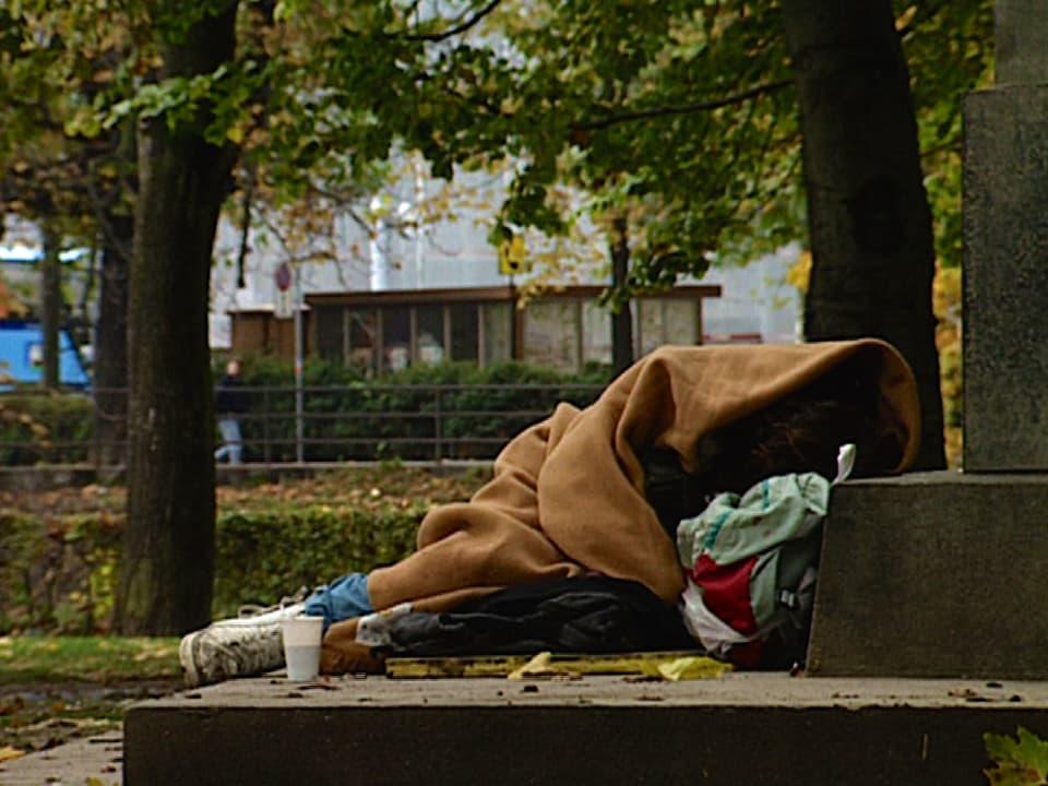 Verwahrloster Junkie am Platzspitz, eingehüllt in eine Decke, nur die Füsse schauen heraus.