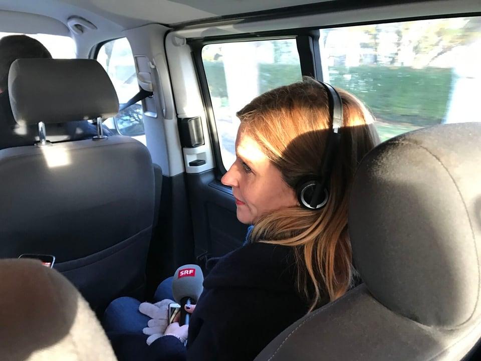 Sabine Dahinden sitzt im Auto mit Kopfhörer und Mikrofon.