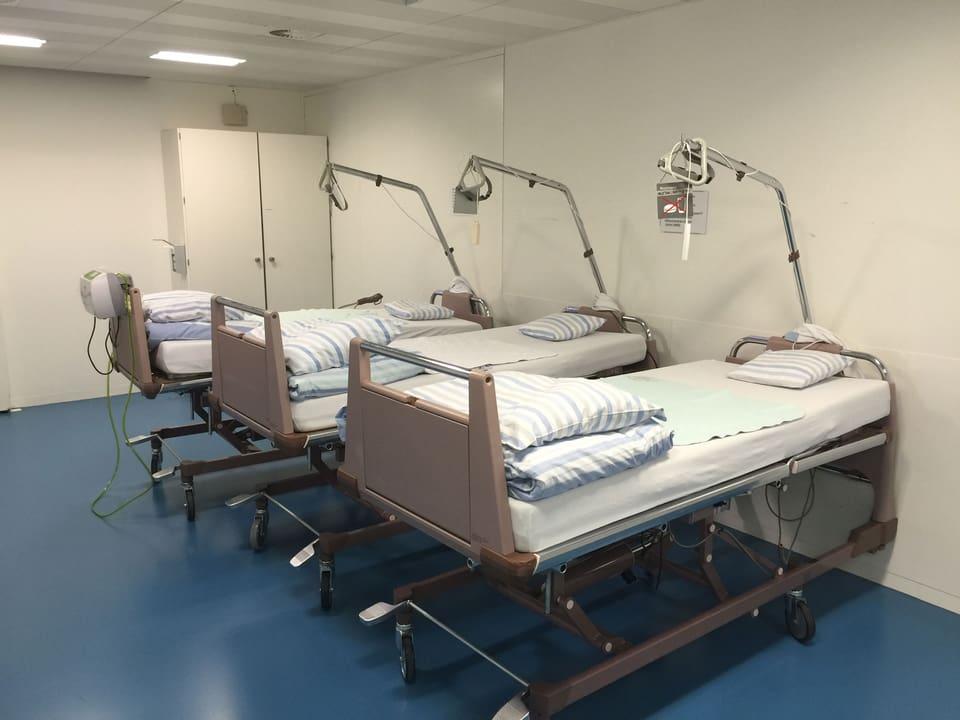 Drei Spitalbetten stehen in einem Raum bereit.