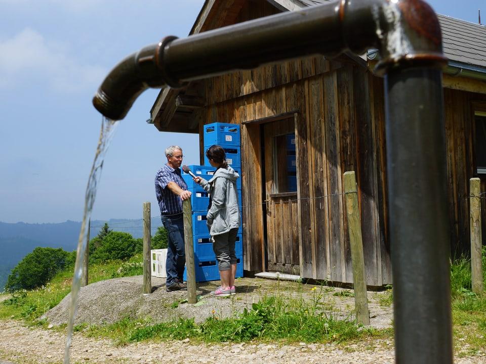 Im Vordergrund fliesst Wasser aus einem Hahn in den Brunnen, im Hintergrund sind die zwei Personen vor dem Hüttli im Gespräch.