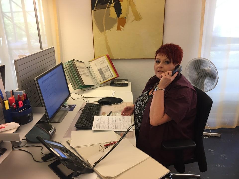 Frau im Büro am Telefon.