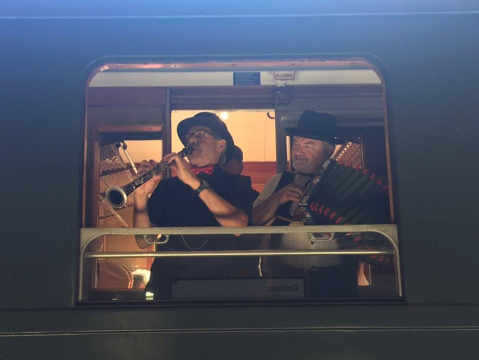 Im Zugfenster sieht man zwei Musikanten