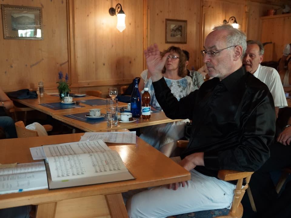 Der Dirigent sitzt mit erhobener Hand an einem Tisch, auf dem Notenblätter liegen.