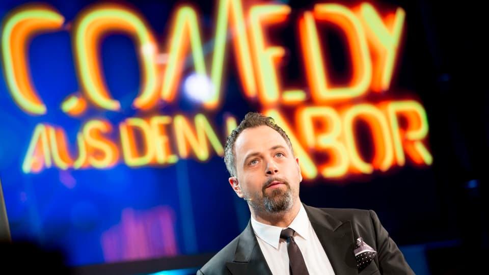 """Michel Gammenthaler steht vor dem Signet """"Comedy aus dem Labor"""