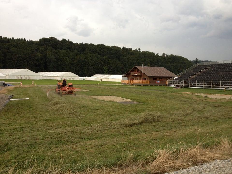 Blick auf Gelände mit Chalet und Festzelten im Hintergrund.