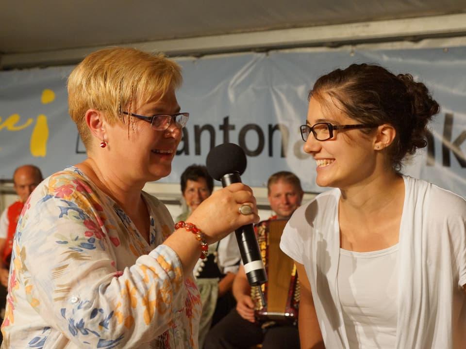 Christine Gertschen mit Mikrofon und eine Älplerin.