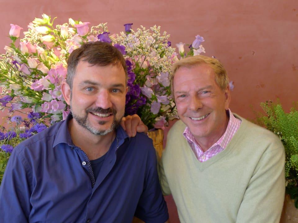 Besitzer Frank Wössner (links) und Kurt Aeschbacher (rechts) lächeln in die Kamera. Im Hintergrund die imposanten Glockenblumen in weiss, violett und lila Tönen.
