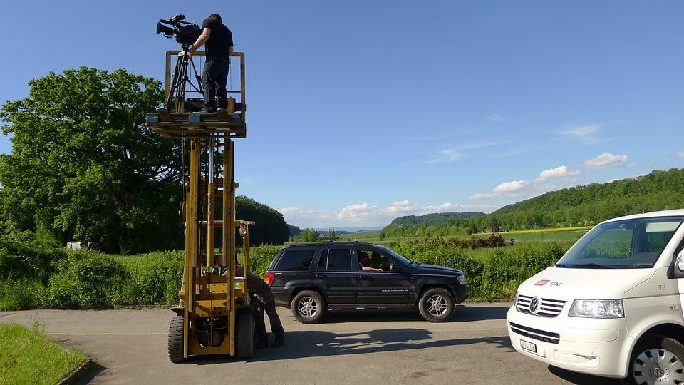 Im Freien wird ein Gabelstapler eingesetzt. Der Kameramann befindet sich mit Kamera und Stativ auf dem Plateau in ca. 5 m Höhe. Rechts im Bild ist der Vorderteil des mit SRF tpc beschrifteten weissen VW-Busses zu sehen.