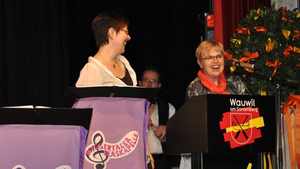 Karin Kobler und Christine Gertschen lachend am Rednerpult beim Galaabend «20 Jahre IG Schweizer Blaskapellen».