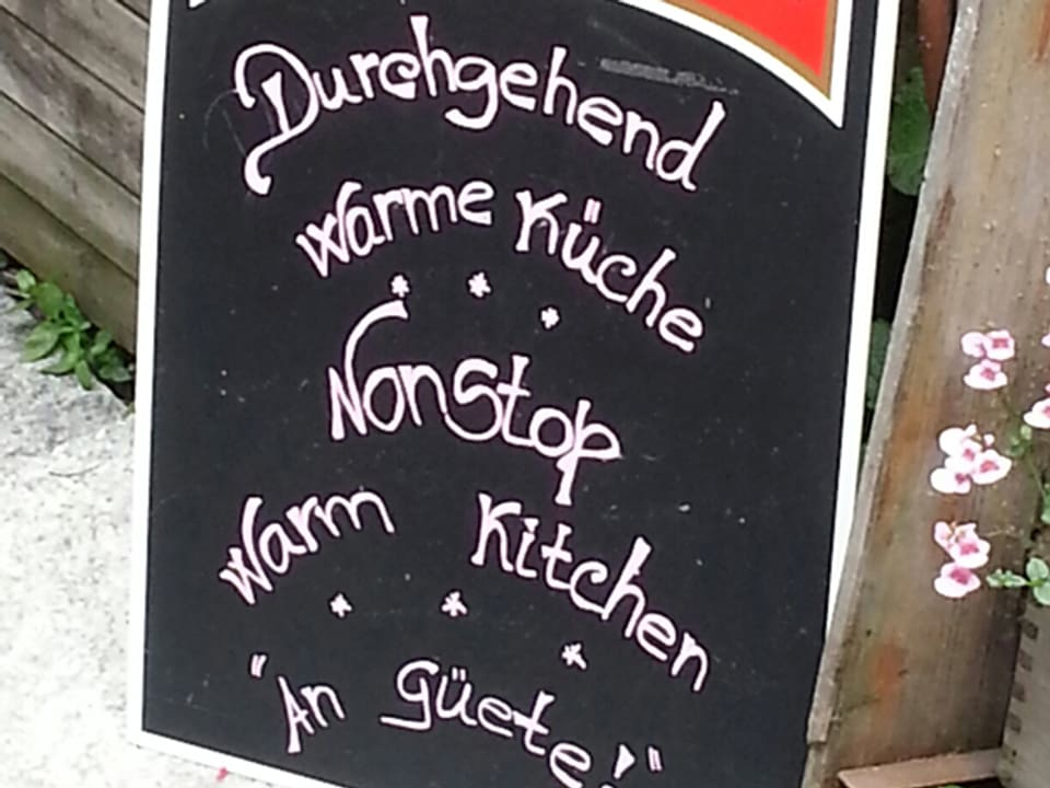 Schild mit der Aufschrift «Durchgehend warme Küche» – «Nonstop warm kitchen».