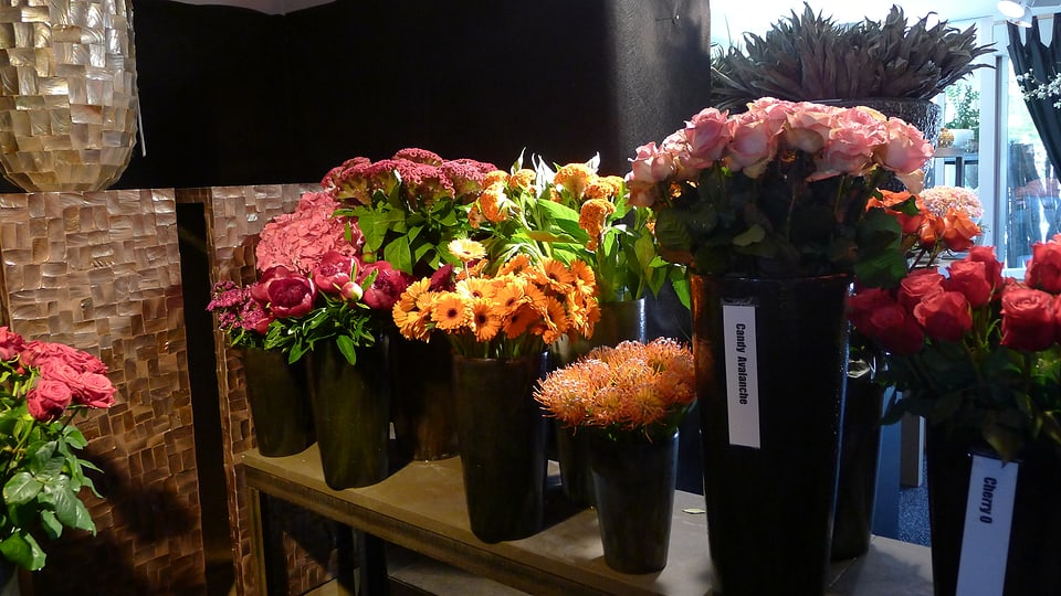 Diverse schlanke schwarze Blumengefässe mit jeweils einem Strauss gleicher Blumen, in den Farben rot, gelb, orange gehalten, stehen auf einem schmalen Holztisch.