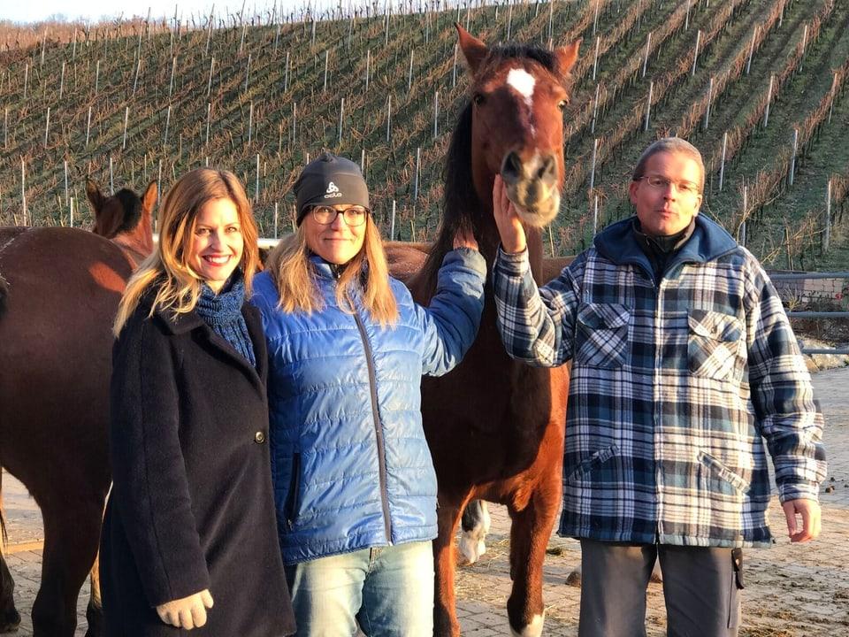 Sabine Dahinden posiert mit zwei Freiwilligen und einem Pferd.