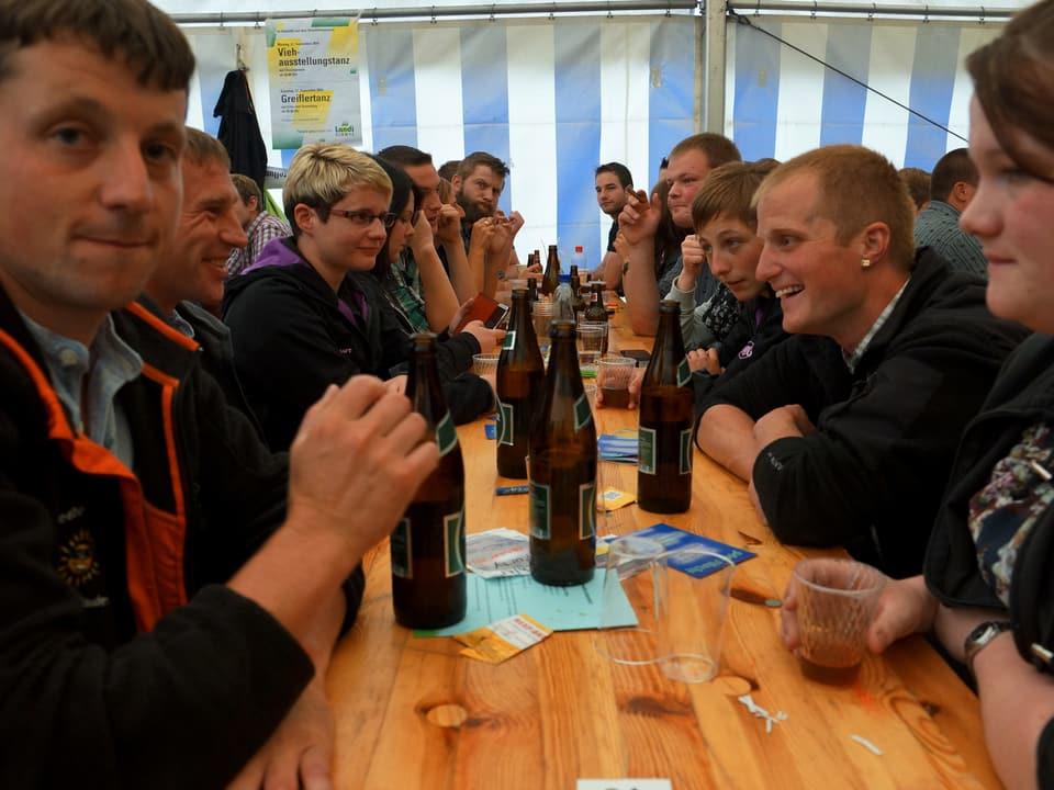 Eine fröhliche Runde mit jungen Leuten sitzt am Tisch und spielt einen Jass.