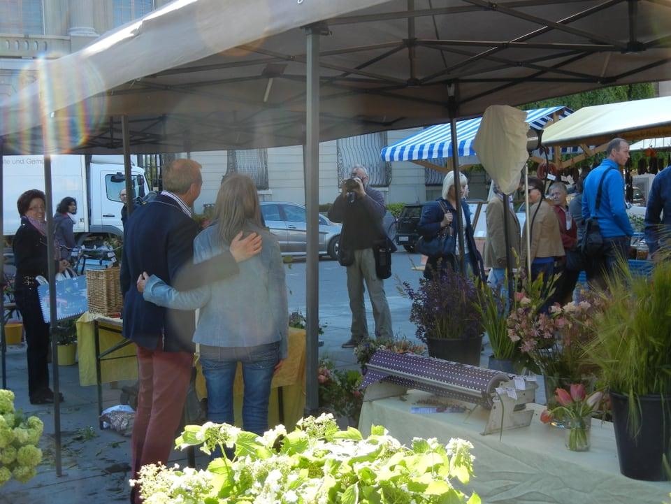 Fotograf Peter Mosimann lichtet Marianne Gnägi und Kurt Aeschbacher ab. Das Paar ist geschützt durch das Dach des Marktstandes. Man sieht sie von hinten. Eine Frau mit Einkaufstasche schaut zu, andere Passanten gehen vorbei.