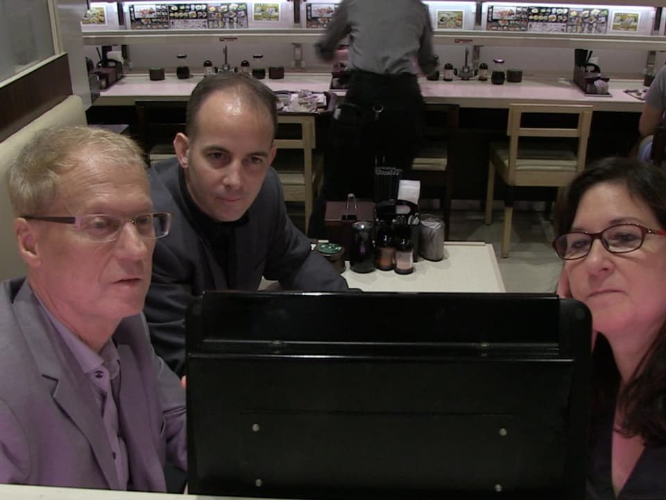 Drei Menschen schauen in Bildschirm.