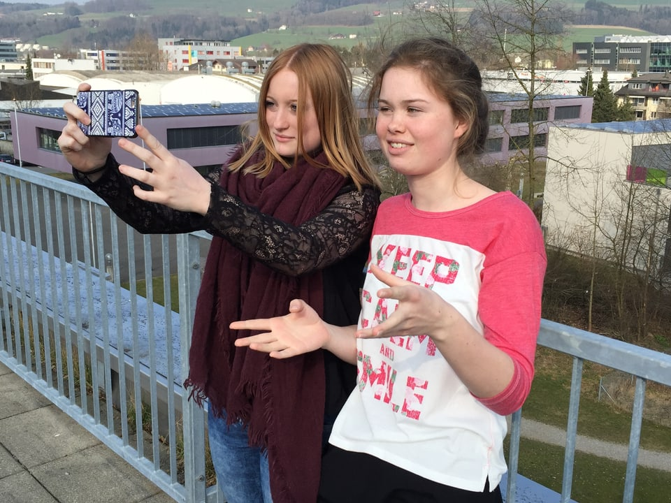 Zwei Mädchen nehmen mit einem Handy ein Video von sich selber auf.