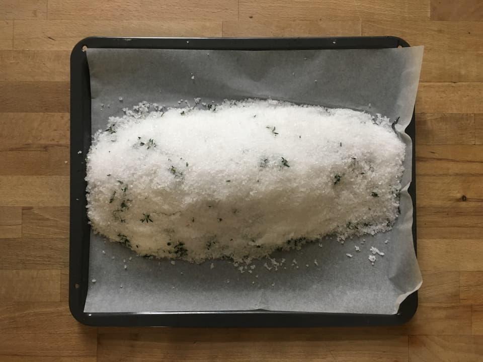 Etwa einen Drittel des Salzes aufs Blech geben und den Felchen darauf platzieren.