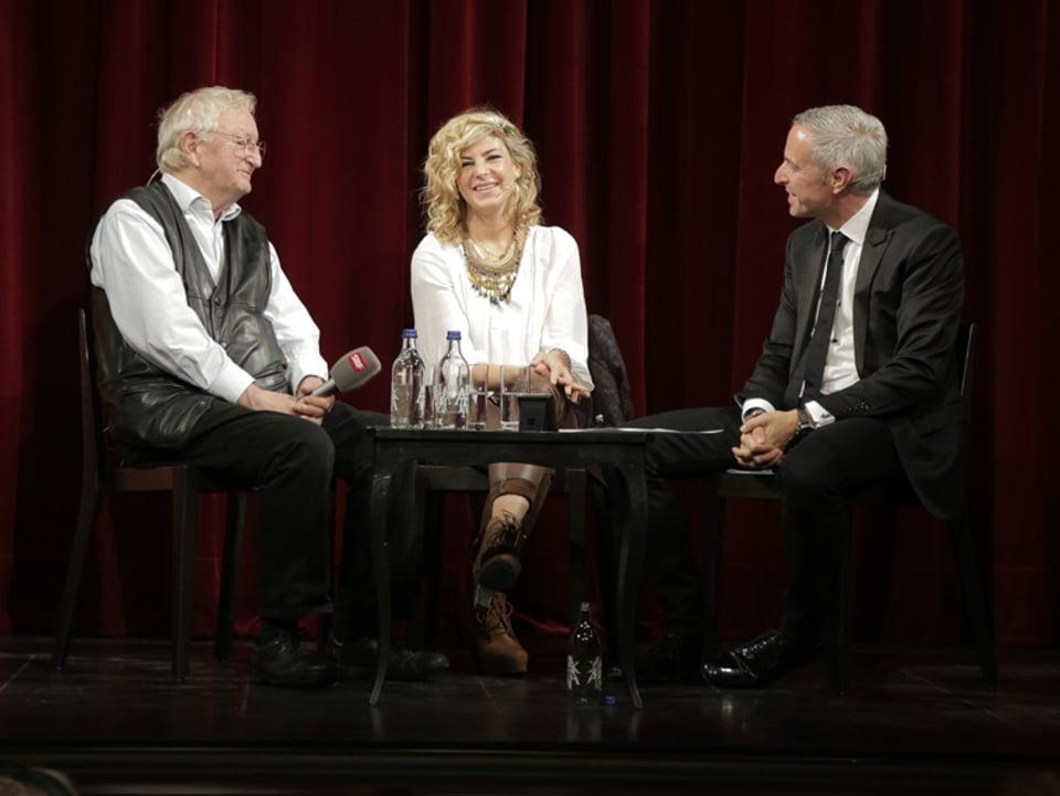 Peter Bichsel, Eliana Burki und Moderator Dani Fohrler vor dem roten Vorhang im Stadttheater Solothurn.