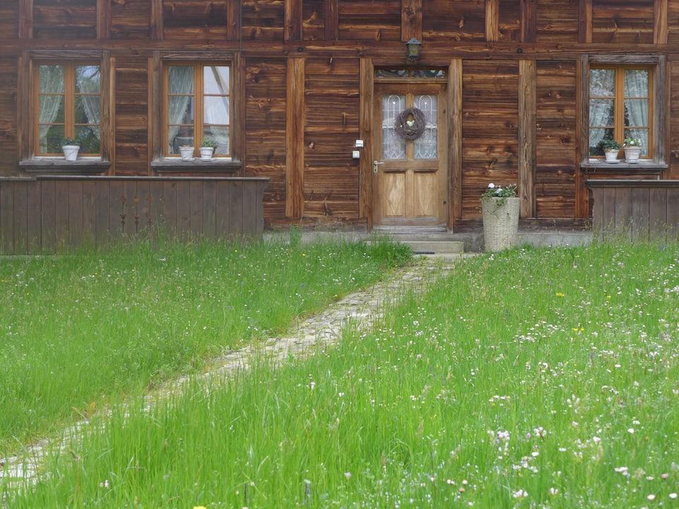 Grüner Wiese vor Holzhaus