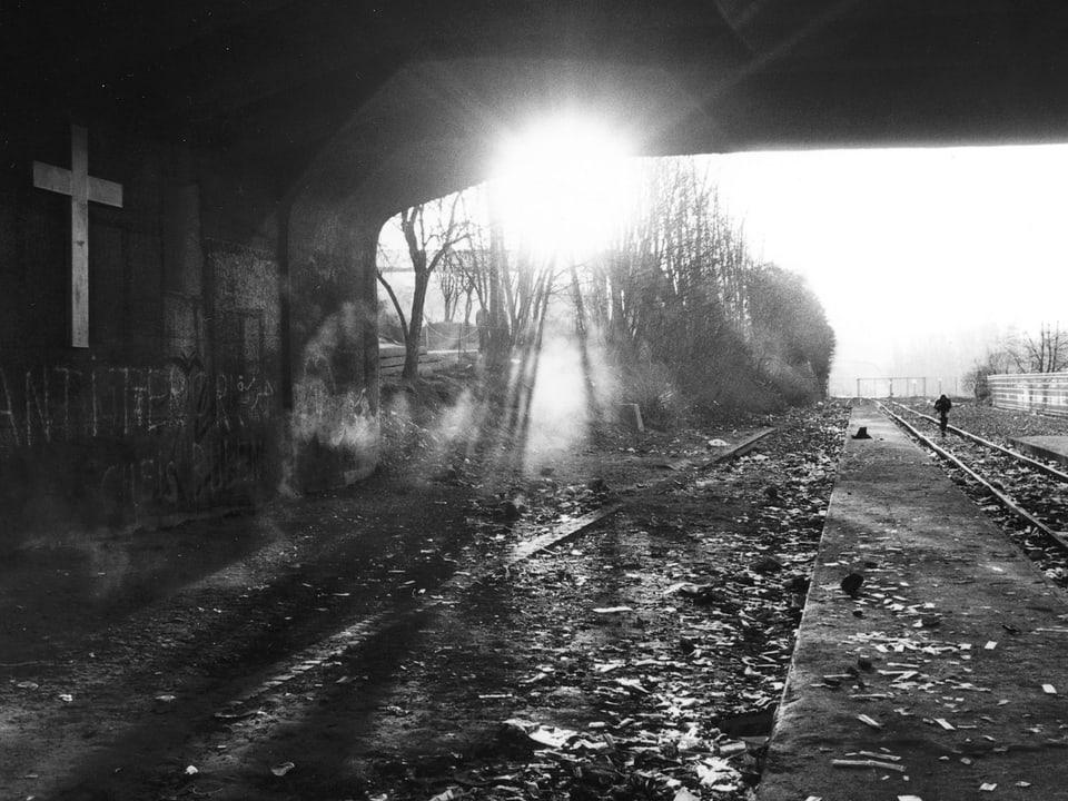 Sonne scheint durch ein Tunnel hindurch. Dreck am Boden. Zuggeleise.