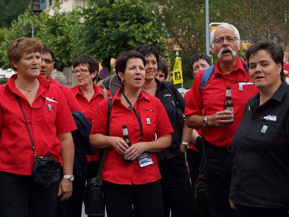 Eine Gruppe von Männern und Frauen in roten Hemden und mit Getränken in den Händen.