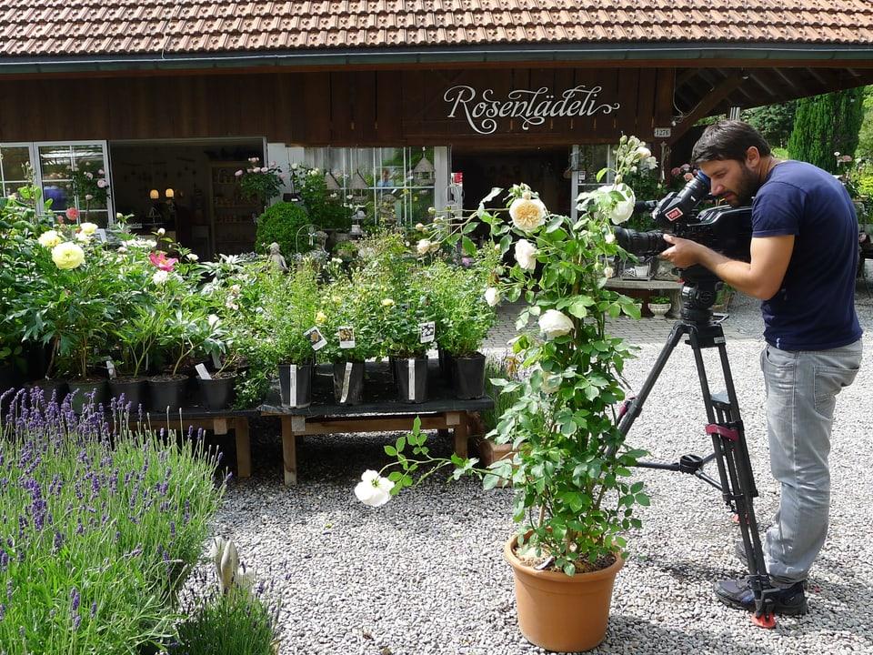 Ueli Haberstich steht auf dem Kiesplatz und filmt mit seiner Kamera auf dem Stativ Rosen. Im Vordergrund ist blühender Lavendel, im Hintergrund der dunkle Verkaufsraum mit weissen Landhausfenstern zu sehen. Über dem Eingang ist mit verschnörkelter weisser Schrift gross «Rosenlädeli» angeschrieben. Diverse Palette mit Kräutern und Blumen stehen zum Verkauf bereit.