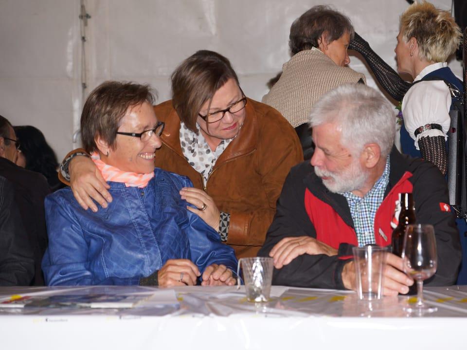 Besucherinnen und Besucher, die sich im Festzelt vergnügt unterhalten.