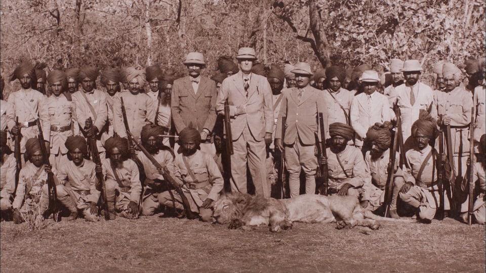 Englische Kolonialherren posisieren mit totem Löwen