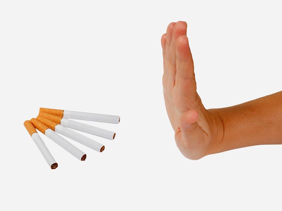 Eine Hand wehrt sich gegen fünf Zigaretten, die bereitliegen.