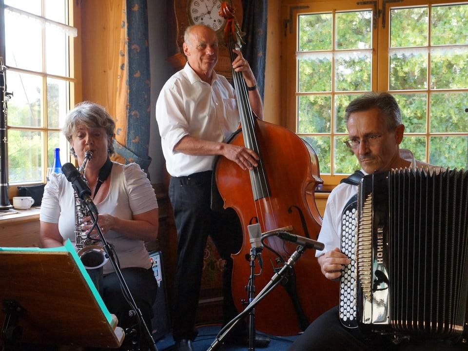 Saxophonspielerin, Kontrabassist und Akkordeonist spielen als Trio in der Gaststube.