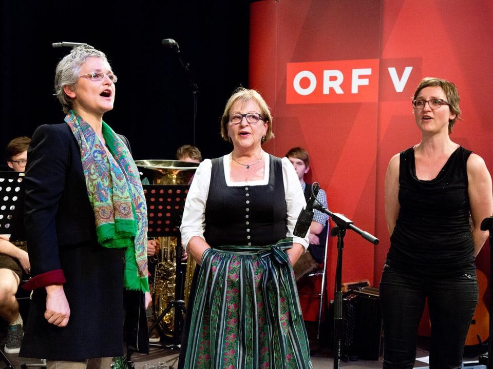 Drei singende Frauen während ihres Auftritts.