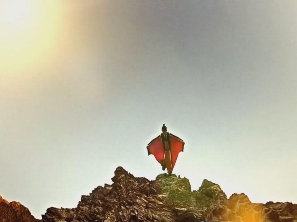 Mann im Wingsuit springt vom Felsen.