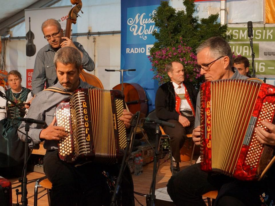 Ein Musiker mit Kontrabass und zwei Musiker mit Akkordeon beim Auftritt im Festzelt.