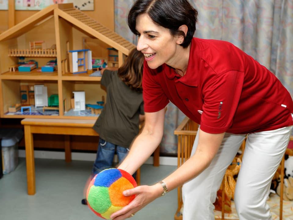 Freiwillige Helferin spielt Ball mit Kind. Im Hintergrund ein kleines Mädchen, das mit grossem Holz-Puppenhaus spielt.