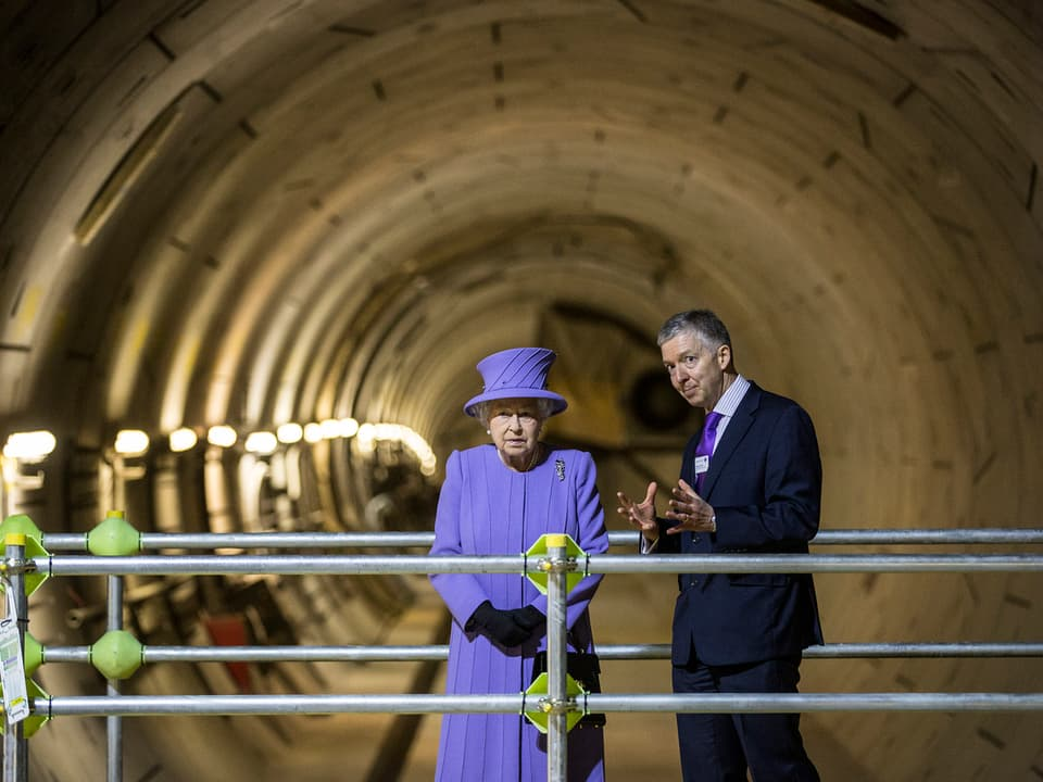 Die Queen in einer Untergrundbahnröhre stehend.