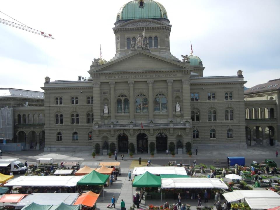 Vor dem Bundeshaus Bern sind Marktstände mit verschiedenfarbigen Dächern und Formen aufgebaut. Der Markt scheint gut besucht.