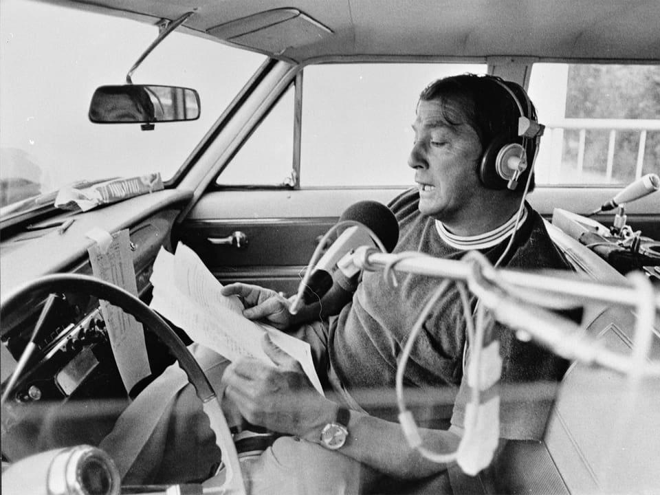 Sepp Renggli im Auto, das Mikrofon wird durchs Fenster gereicht.